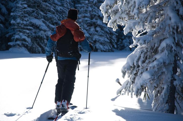 雪道をスキーで歩く人